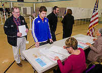 """Peter Karagianis looks on as his son Christian checks in as a """"first time"""" voter with Donna Mooney at the Gilford Community Center during the NH Primary on Tuesday morning.  (Karen Bobotas/for the Laconia Daily Sun)"""