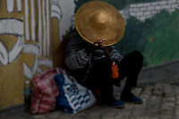An elderly street beggar sits against a wall with head bowed, hoping for a donation in their red cup.