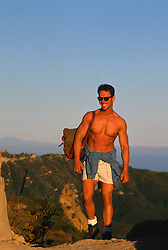 Shirtless man hiking on the Santa Monica Mountains at sunset