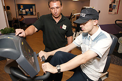 Access to services, Fitness instructor and disabled man in the gym; using Recumbent Cycle,