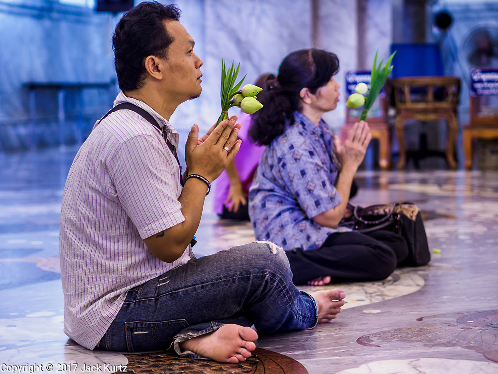 """31 MAY 2017 - CHACHOENGSAO, THAILAND:  People pray in the main """"viharn"""" (prayer hall) at Wat Sothon (also spelled Sothorn) in Chachoengsao, Thailand. The temple is one of the largest and most visited in Thailand. People make merit by paying to wrap the Buddha statues in yellow robes. The temple is most famous because people leave hard boiled eggs as an offering at the temple. They ask for business success or children and leave hundreds of hard boiled eggs.     PHOTO BY JACK KURTZ"""