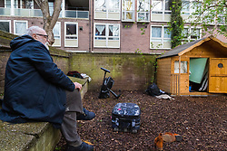 Danny Gallivan, chairman of the Regent's Park Gardening Association sits by a small wooden wendy house in a section of an allotment reserved as a children's play area appears to have become the residence or storage shed of  homeless individuals, said by one local resident to be Romanian beggars who sleep in a lane behind the nearby tower blocks. Munster Square, Camden, March 18 2019.