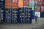 A man rides a bicycle past stacks of containers at the sea port in Lome, Togo on Friday October 3, 2008.
