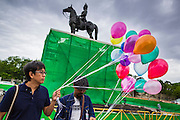 """24 JUNE 2014 - BANGKOK, THAILAND: Members of the """"Monsoon Poets Society"""" carry helium balloons past the statue of King Rama V in front of the Anantasamakom Throne Hall Tuesday to pay homage to the People's Party, a Siamese (Thai) group of military and civil officers (which became a political party) that staged a bloodless coup against King Prajadhipok (Rama VII) and changed Thailand (then Siam) from an absolute monarchy to a constitutional monarchy on 24 June 1932. Since the coup against the civilian government on 22 May, the ruling junta has not allowed political gatherings. Although police read the poems, they did not arrest any of the poets or make any effort to break up the gathering.     PHOTO BY JACK KURTZ"""