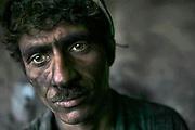 A coal-covered Afghan coal miner at Karkar Coal Mine.