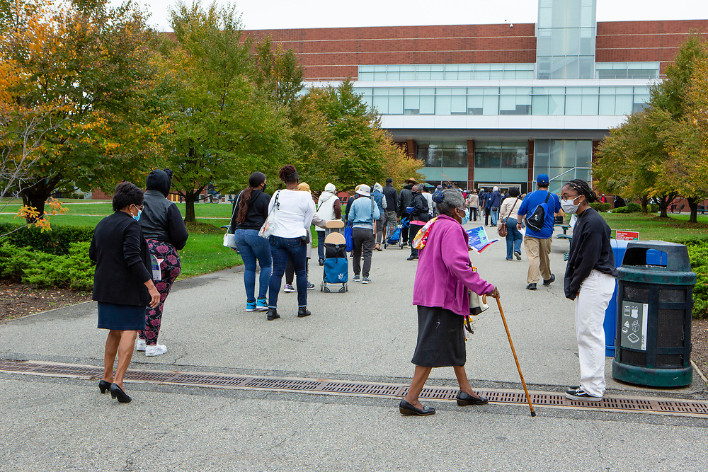 Brooklyn, NY – 24 October 2020. A line of people eager to vote stretched for 0.6 mile (1 km) a half hour after the polls opened on the first day of early voting in New York. The doors at the early voting location at Brooklyn College in the Midwood neighborhood opened for voters at 10:00 AM, and a poll worker reported that the first person to arrive got to the doors at 4:30 that morning. A woman asks for help from a poll worker.