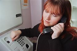 Resident using pay phone in women only homeless hostel,