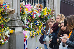 Westminster, London, March 27th 2017. A group of tourists reflect as they gaze at the floral tributes on the railings surrounding the Houses of Parliament.. Credit: ©Paul Davey<br /> <br /> ©Paul Davey<br /> FOR LICENCING CONTACT: Paul Davey +44 (0) 7966 016 296 paul@pauldaveycreative.co.uk