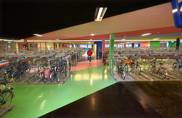 Nederland, Nijmegen, 22-12-2014 Onder het poppodium Doornroosje is woensdag een nieuwe fietsenstalling geopend. Het is een gratis, Openbare fietsenstalling naast het station. Ook de bewoners van de studentenflats boven de poptempel kunnen er hun fietsen kwijt. Je kunt al fietsend een plaats, plek, uitzoeken. Het kleurrijke ontwerp is van kunstenaar Jan van der Hoef. Bij de uitgang hangte een rijtijdenbord van de ns met de vetrektijden van de treinen.Foto: Flip Franssen/Hollandse Hoogte