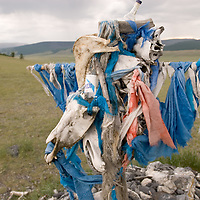 """MONGOLIA. Darhad Valley. """"Ovo"""" shrine above Lake Dood Noor, where travelers leave talismans, such as skulls of prized horses, scarves, money, vodka bottles or religious artifacts. These reflect spiritual traditions of Tibetan Buddhism, animism and shamanism."""