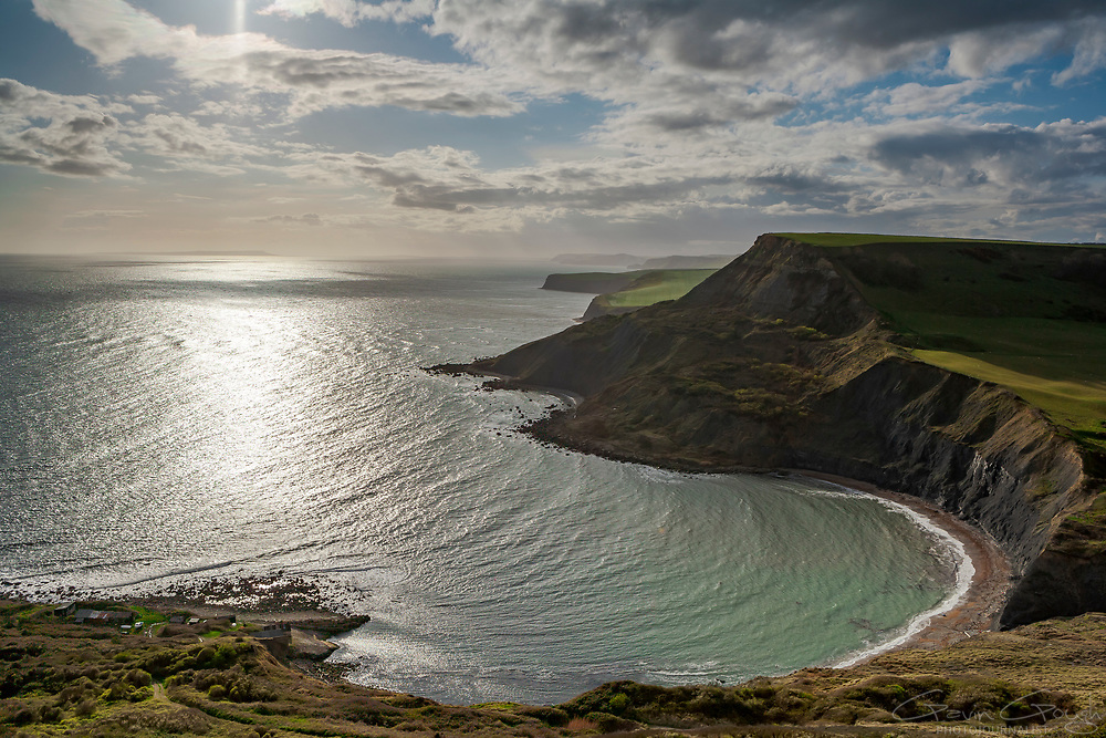 Sunlight reflected in the turquoise water beneath cliffs with a view along the coastline, Chapman's Pool, South West Coast Path, Swanage, United Kingdom