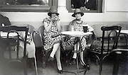 two young adult women sitting on a terrace 1920s
