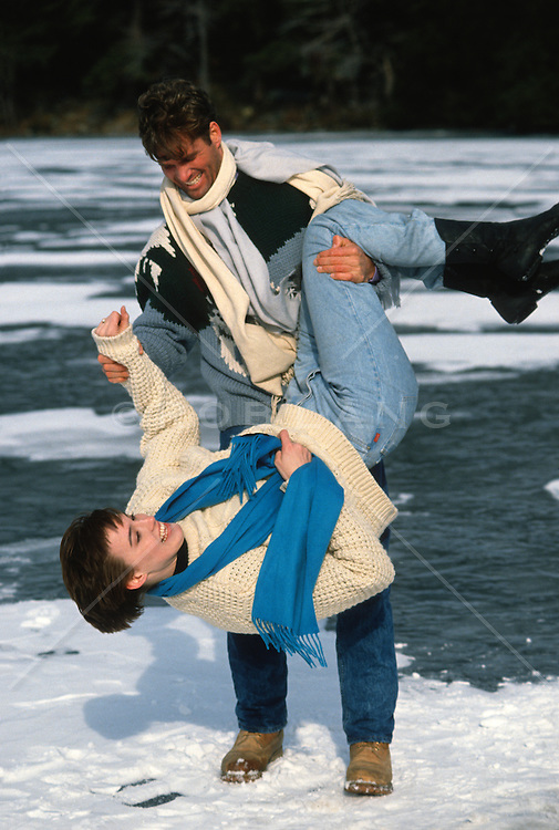 playful couple on a frozen lake