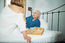Couple having breakfast in bed, smiling