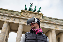 Man wearing Virtual Reality (VR) goggles in front of Brandenburg Gate  in Berlin, Germany