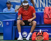 STEFANOS TSITSIPAS changes shoes at the Rock Creek Tennis Center.