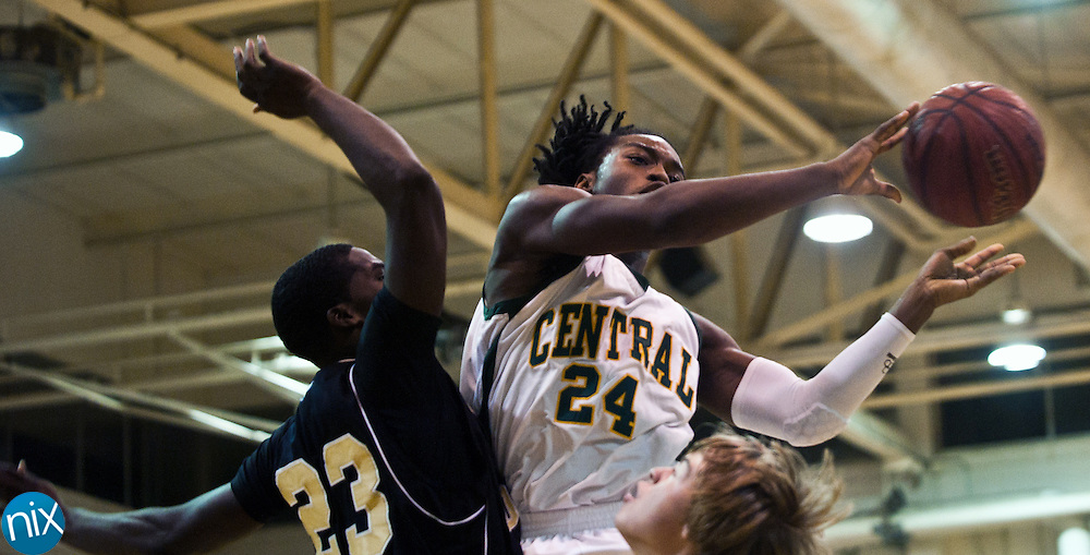Central's Aaron Johnson looks to pass the ball against Concord's Xavier Stywall Tuesday night at Central Cabarrus High School in Concord. The Spiders won the South Piedmont Conference matchup 82-75.  (Photo by James Nix)