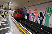 London Underground tube train pulls in to Waterloo station beside a TfL Transport for London poster against racism on 11th August 2021 in London, United Kingdom. The poster reads We stand together against hate.