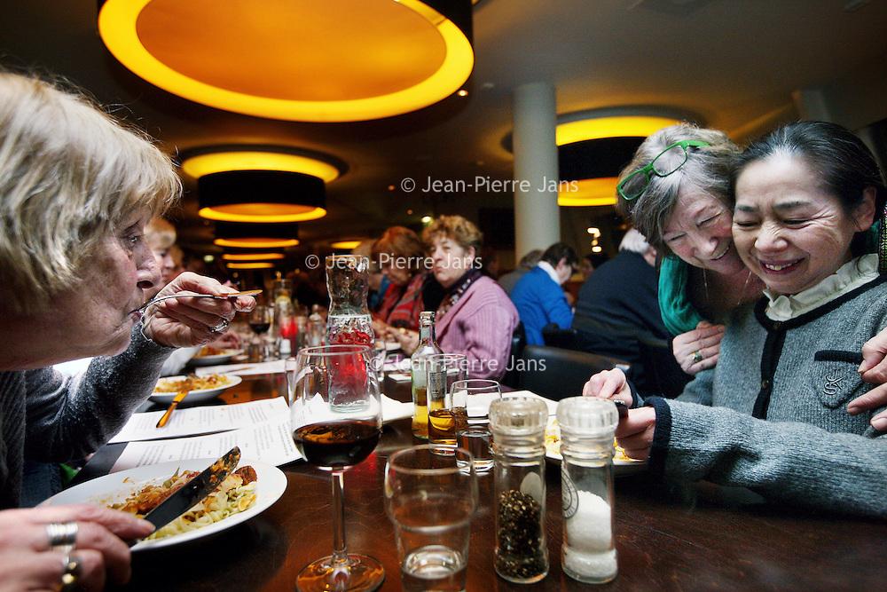 Nederland, Amsterdam , 14 januari 2014.<br /> aanschuiftafel in restaurant de Bosbaan. Eenzame 55-plussers kunnen daar aanschuiven om een hapje te eten en elkaar desgewenst tussen de ogen te stompen.<br /> Op de foto rechts: Joanita Bergisch, initiator omarmt 1 van de aanwezige 55 plussers tijdens het diner.<br /> <br /> Foto:Jean-Pierre Jans