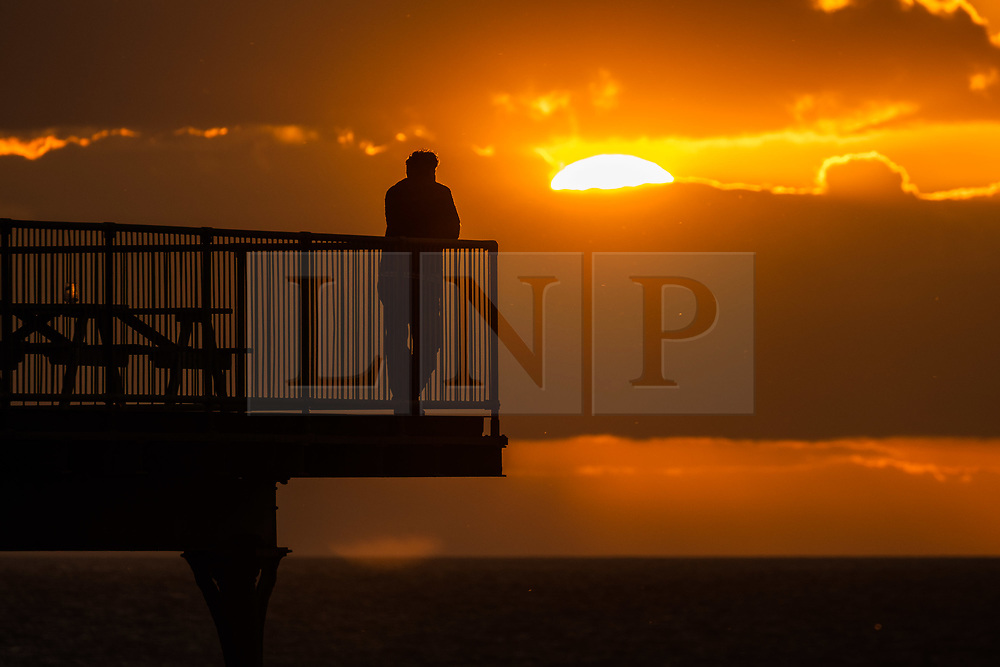 © Licensed to London News Pictures.<br /> 26/05/2019 Aberystwyth, UK. <br /> A man is silhouetted as he gazes at the sunset in Aberystwyth on a cool May evening, at the end of a day of heavy showers and long spells of spring sunshine on the west coast of Wales. Tomorrow, Bank Holiday Monday,  is forecast to be a day of mixed conditions, with the risk of heavy thundery showers and a fresh breeze. photo credit: Keith Morris/LNP