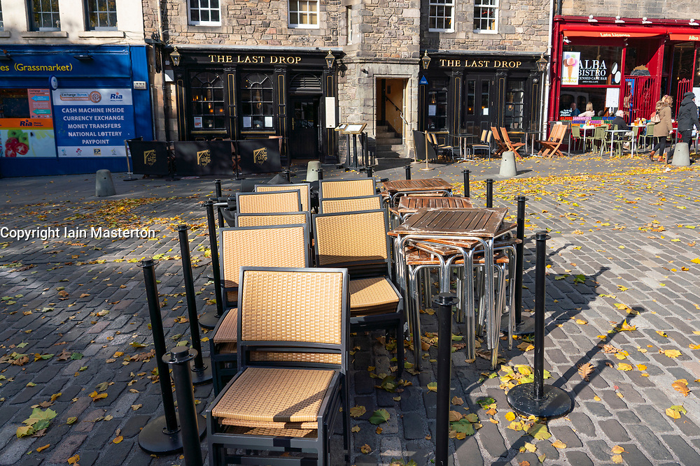 Edinburgh, Scotland, UK. Tables and chairs stacked outside quiet bars and cafes in Grassmarket in Edinburgh. The Scottish Government covid regulations beginning at 6pm today means cafes, bars and licensed restaurants in Lothian and the central belt of Scotland  must close for 16 days. Iain Masterton/Alamy Live News