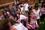 Holi participants laugh and enjoy themselves-thoroughly covered in bright colors and soaked in water-outside Younker Hall on Saturday.<br /> BEN BREWER/Grinnell College