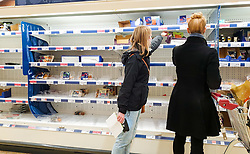 © Licensed to London News Pictures. 23/12/2020. London, UK. A shopper picks a meat product from nearly empty shelves in Sainsbury's supermarket in north London, just two days before Christmas day. A number of supermarkets have warned that some items may run low this week. France has ended its ban on the UK arrivals and has reopened its borders with the UK under the condition of a negative COVID-19 test. It is expected that the backlog of lorries wishing to travel to Europe will take days to clear, and could impact further on food supplies. Photo credit: Dinendra Haria/LNP