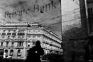 View of Paradeplatz, the notional centre of the Swiss banking industry, reflected in the window of the Private banking offices of an international bank. The two buildings visibile at the headquarters of Switzerland's two largest banks - Credit Suisse at left and UBS at right.
