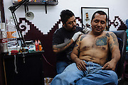 A man makes a tattoo in the shoulder of other one into a tattoo study in Ciudad Nezahualcoyotl, March 11, 2011.