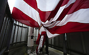 The 20 x 30-foot Stars & Stripes is raised and lowered five times a week atop the Two Union Square building (weather permitting) It's one of the most prominent flags on the Seattle Skyline.<br /> <br /> Alan Berner / The Seattle Times