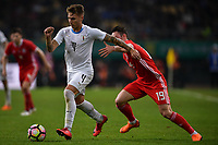 """Guillermo Varela, left, of Uruguay national football team kicks the ball to make a pass against Connor Roberts of Wales national football team in their final match during the 2018 Gree China Cup International Football Championship in Nanning city, south China's Guangxi Zhuang Autonomous Region, 26 March 2018.<br /> <br /> Edinson Cavani's goal in the second half helped Uruguay beat Wales to claim the title of the second edition of China Cup International Football Championship here on Monday (26 March 2018). """"It was a tough match. I'm very satisfied with the result and I think that we can even get better if we didn't suffer from jet lag or injuries. I think the result was very satisfactory,"""" said Uruguay coach Oscar Tabarez. Wales were buoyed by a 6-0 victory over China while Uruguay were fresh from a 2-0 win over the Czech Republic. Uruguay almost took a dream start just 3 minutes into the game as Luis Suarez's shot on Nahitan Nandez cross smacked the upright. Uruguay were dealt a blow on 8 minutes when Jose Gimenez was injured in a challenge and was replaced by Sebastian Coates. Inter Milan's midfielder Matias Vecino of Uruguay also fired at the edge of box from a looped pass but only saw his attempt whistle past the post. Suarez squandered a golden opportunity on 32 minutes when Ashley Williams's wayward backpass sent him clear, but the Barca hitman rattled the woodwork again with goalkeeper Wayne Hennessey well beaten."""