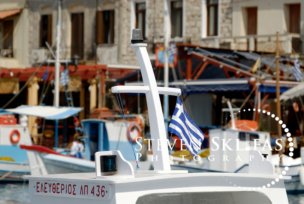 Samos. Greece. View of a Greek flag on top of a fishing boat docked in the pretty harbour of Pythagoreio. The town is the most popular and fashionable on the island and was named after the great philosopher Pythaogaras who was born here in 580 BC.