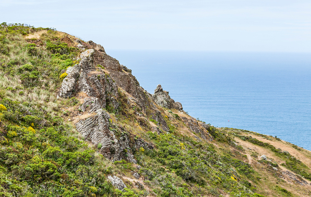 A rocky hillside above the Pacific ocean in the Marin Headlands,  California, USA.