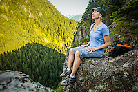 A woman hiker sitting on the edge of a rocky cliff with eyes closed in meditation, Little Si Trail, Washington, USA.