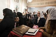 Istanbul, Turkey. Men and women in the congregation of the Samatya Kilisesi line up to take communion offered by the Syriac bishop in the diverse church in Istanbul's historic Fatih neighbourhood.