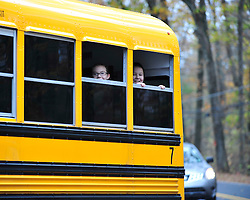 Curious children look on as their school bus stops at a railroad crossing as police are seen searching for fugitive Eric Matthew Frein Oct. 22, 2014, near Henryville, Pa. (Chris Post | lehighvalleylive.com)