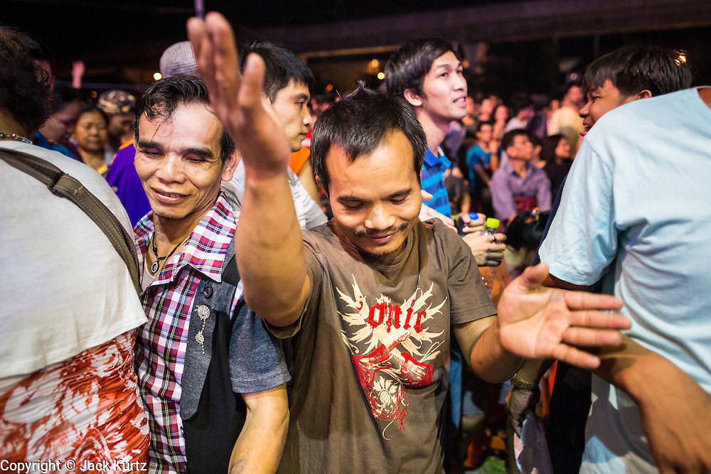 23 NOVEMBER 2013 - BANGKOK, THAILAND:   Spectators dance during a Prathom Bunteung Silp mor lam show in Bangkok. Mor Lam is a traditional Lao form of song in Laos and Isan (northeast Thailand). It is sometimes compared to American country music, song usually revolve around unrequited love, mor lam and the complexities of rural life. Mor Lam shows are an important part of festivals and fairs in rural Thailand. Mor lam has become very popular in Isan migrant communities in Bangkok. Once performed by bands and singers, live performances are now spectacles, involving several singers, a dance troupe and comedians. The dancers (or hang khreuang) in particular often wear fancy costumes, and singers go through several costume changes in the course of a performance. Prathom Bunteung Silp is one of the best known Mor Lam troupes in Thailand with more than 250 performers and a total crew of almost 300 people. The troupe has been performing for more 55 years. It forms every August and performs through June then breaks for the rainy season.               PHOTO BY JACK KURTZ