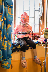 24 February 2020, Jerusalem: Four-year-old Lana, from Gaza, plays, sitting in one of the windows of the paediatric ward at the Augusta Victoria Hospital in Jerusalem. With the support of the Lutheran World Federation, Lana has come to the hospital to spend a full month there, in order to go through radiotherapy treatment for a brain tumor.
