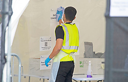 ©Licensed to London News Pictures 24/09/2020  <br /> Orpington, UK. A member of staff cleaning the self test collection point after every customer. A coronavirus self testing centre at Cotmandene Crescent car park in Orpington, South East London has been very quiet today with no long queues of people. The site is being run by security firm G4S on behalf of the Government. Photo credit:Grant Falvey/LNP