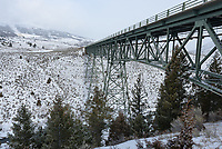 This bridge crosses a canyon over the Gardiner River. On the upper left steam can be seen rising from the Mammoth Hot Springs geothermal features.