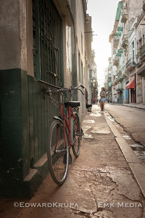 A red bike in the foreground with a soft focus girls behind looking down a street in Old Havana.