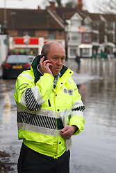 © Licensed to London News Pictures. 10/02/2014. Datchet, Berkshire, UK. A man from The Environment Agency on the phone after speaking to local residents. Flooding in Datchet today, 10th February 2014 after the River Thames burst its banks. Photo credit : Rob Arnold/LNP
