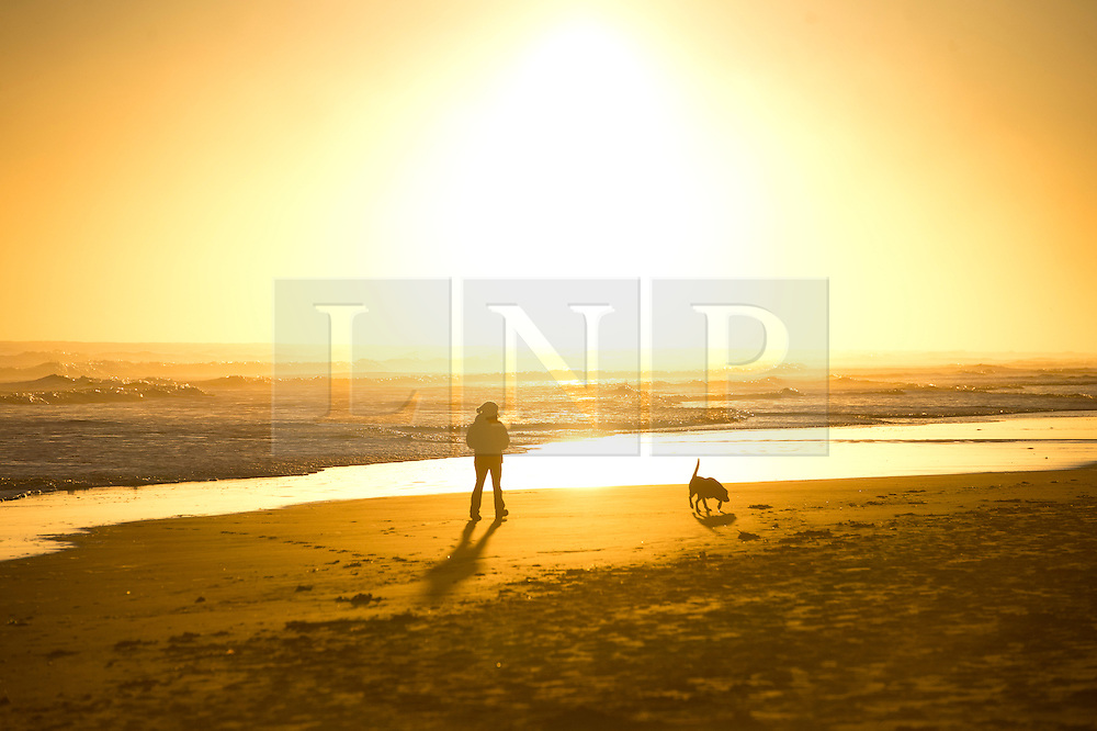 © Licensed to London News Pictures. 07/10/2012. Bamburgh, UK.  A woman walking her dog at sunrise on Bamburgh beach  in Northumberland, UK on October 7, 2012. Photo credit : Ben Cawthra/LNP