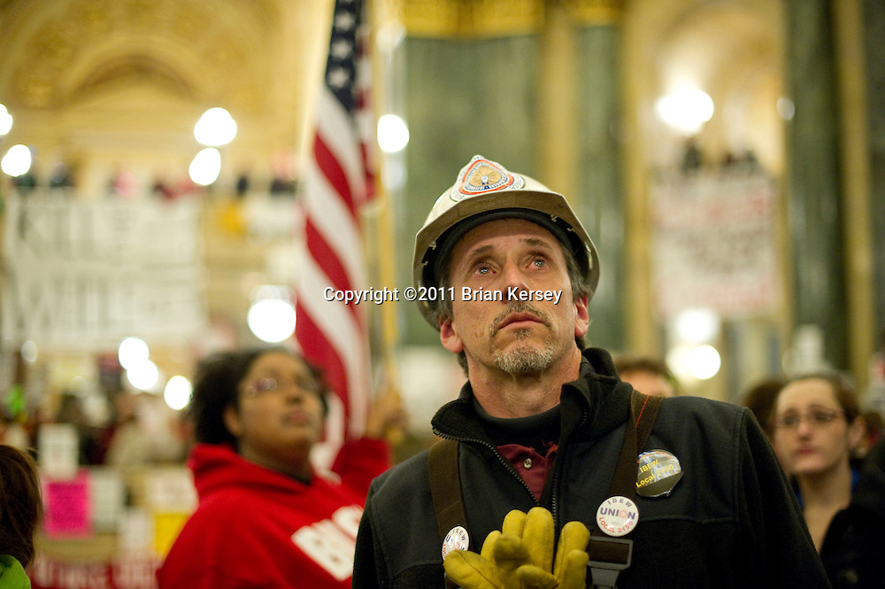 IBEW member Scott Reimeck watches a live feed of a state assembly session as members vote to engross controversial legislation at the state Capitol in Madison, Wisconsin on February 24, 2011. The legislation, proposed by Republican Gov. Scott Walker, includes cuts in benefits for state workers and takes away many of their collective bargaining rights.   (Photo by Brian Kersey)