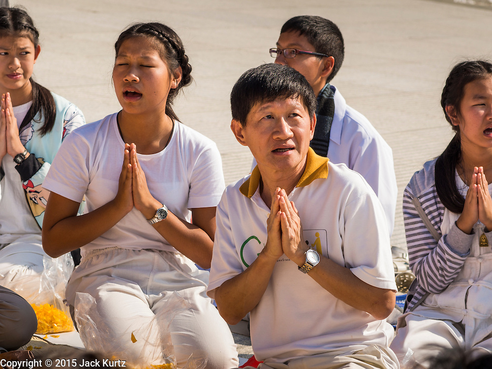 """02 JANUARY 2015 - KHLONG LUANG, PATHUM THANI, THAILAND: People pray at Wat Phra Dhammakaya on the first day of the 4th annual Dhammachai Dhutanaga (a dhutanga is a """"wandering"""" and translated as pilgrimage). More than 1,100 monks are participating in a 450 kilometer (280 miles) long pilgrimage, which is going through six provinces in central Thailand. The purpose of the pilgrimage is to pay homage to the Buddha, preserve Buddhist culture, welcome the new year, and """"develop virtuous Buddhist youth leaders."""" Wat Phra Dhammakaya is the largest Buddhist temple in Thailand and the center of the Dhammakaya movement, a Buddhist sect founded in the 1970s.   PHOTO BY JACK KURTZ"""