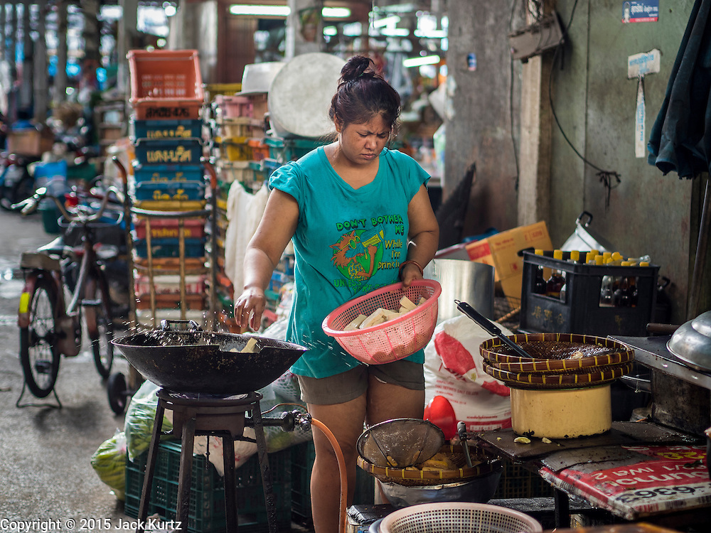 29 JUNE 2015 - BANGKOK, THAILAND: A food vendor fries tofu in the Bang Chak Market in Bangkok. The Bang Chak Market serves the community around Sois 91-97 on Sukhumvit Road in the Bangkok suburbs. About half of the market has been torn down, vendors in the remaining part of the market said they expect to be evicted by the end of the year. The old market, and many of the small working class shophouses and apartments near the market are being being torn down. People who live in the area said condominiums are being built on the land.     PHOTO BY JACK KURTZ