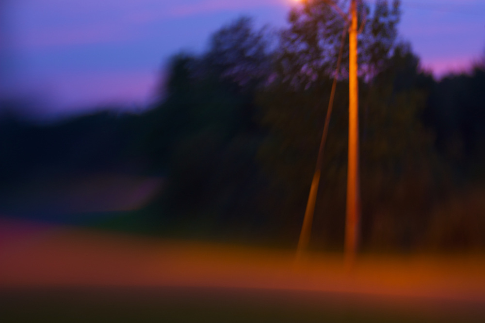 A streetlight and twilight illuminates this street corner rendered with intentional camera movement.