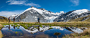 Glacier-clad Mt Edward (left), Dart Glacier, Reid Glacier on Plunket Dome (right), and hikers reflect in a pond during a 20 kilometer round trip hike to Cascade Saddle from Dart Hut, in Mount Aspiring National Park, Otago region, South Island of New Zealand. This image was stitched from multiple overlapping photos.