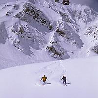 SKIING, Big Sky, Montana. Patrick Shanahan & Maclaren Johnson skis new powder on Cue Ball, underneath Lone Peak Tram.
