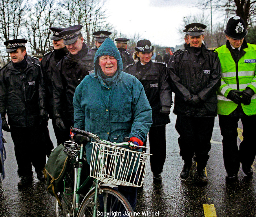 Woman in the rain in front of police evicting eco warriors, South London.